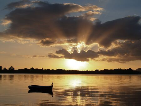 Daybreak over the bay, rising sun silhouettes dinghy at rest. photo