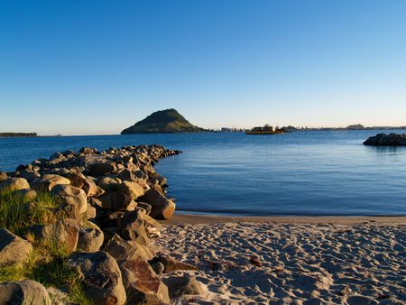 The Mount across the harbour, beach and rock foreground 版權商用圖片 - 4575196