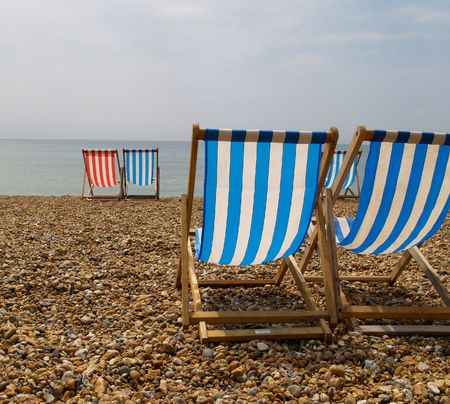 Striped deckchairs at beach, with one red.