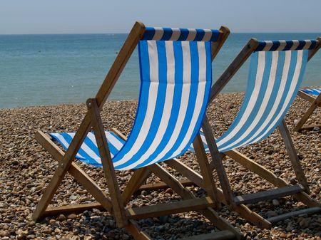 Two deckchairs on beach photo
