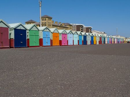 Brightly coloured beach huts on esplanade foreground. photo