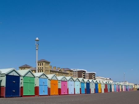 Beach huts lined uunder clear blue sky.