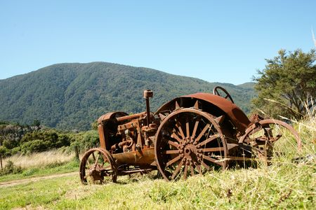 old tractor: Vintage tractor rusting away on a New Zealand farm. Stock Photo