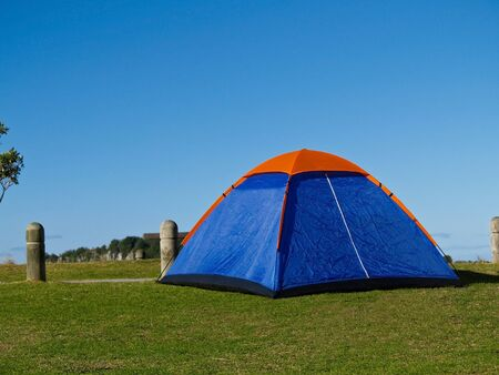 holidaying: Small blue tent with an orange peak erected at beachside camping ground, Mount Maunganui, New Zealand.
