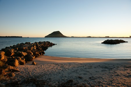 Harbour view to Mount Maunganui and Tauranga entrance as the sun rises. Stock Photo