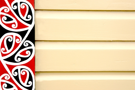 Traditional maori design as vertical frieze on building, close up.