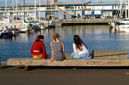 Wellington, New Zealand, October 4 2010, friends sitting on the dock
