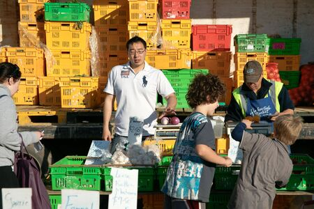 Wellington farmers market, New Zealand, October 4 2010, vendors greet buyers at their stall, with colored vegetable crates stacked behind.