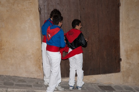 Gubbio, Italy, May 15 2011, young men assis each other in preparations for their part in the Festa Dei Ceri.
