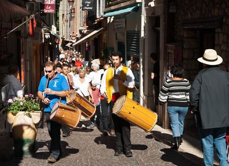 marchers: Antibes, France, May 1, 2011 Marchers beating drums lead crowd in May Day parade..