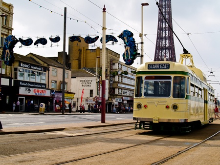 BLACKPOOL, ENGLAND - Starr Gate tram runs along the Promenade, Blackpool Tower in background on June 28, 2009. Trams date back to 1885 and are one of the oldest electric tramways in the world.