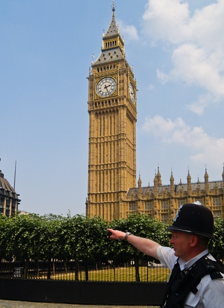 counterterrorism: LONDON, ENGLAND - JULY 3, 2009: London Policeman points the way under Big Ben. Police responsibilities, include co-ordinating and leading on counter-terrorism matters, and helping people on the street.