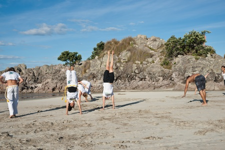 TAURANGA, NEW ZEALAND - JANUARY 23: Group of youths practice the art of capoeira on the Mount Maunganui beach, Tauranga New Zealand on January 23 2012. The sport, founded in Brazil is growing globally. Editorial