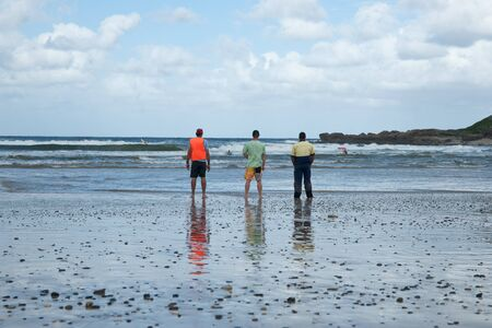 life saving: COFFS HARBOUR, NSW, AUSTRALIA - FEBRUARY 9: Three adults watch surf life saving training on February 9,2012 on beach at Park Beach Coffs harbour, Australia. Coffs Harbour Surf Life Saving Club