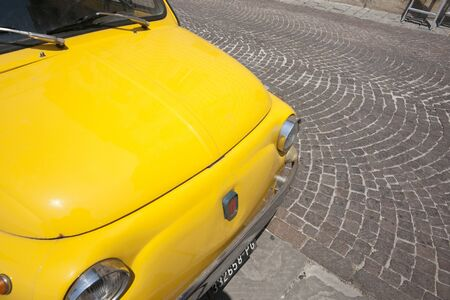 Gubbio, Umbria, Italy, May 13, 2012: the iconic Fiat 500 parked in cobbled street.