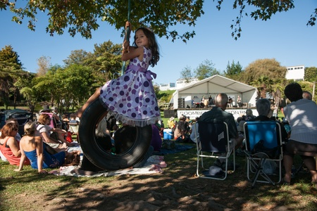 Tauranga, New Zealand, April 9,2012, small girl on a swing in shade of tree, with crowd watching entertaining.
