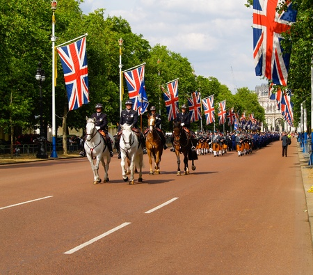 LONDON, ENGLAND - JUNE 15,2009: mounted police lead a group of bagpipers march along London