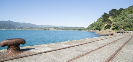 Rail lines and bollard on disused wharf, Hicks Bay, New Zealand