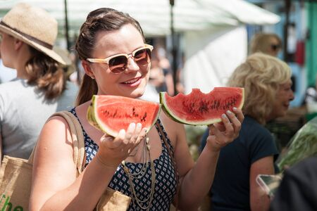 east end: London, England, July 14, 2013; and attractive young woman holds two large watermelon slices in the Columbia Road Flower Markets in East London