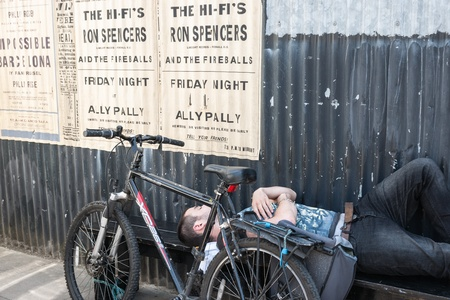alexandra: London, England; July 14, 2013; man asleep on a bench in East London street, his bicycle beside him under aposter for show at the Alexandra Palace  Editorial