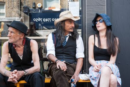 eccentric: London, England; July 15, 2013; Three eccentric looking people sitting outside a shop in East London