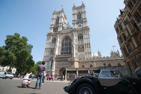 London England - July 19, 2013  Westminster Abbey and tourists with vintage car in foreground in London