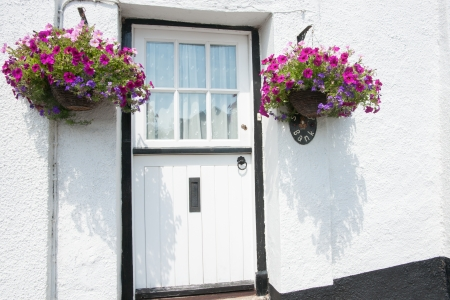 White and black door with hanging baskets