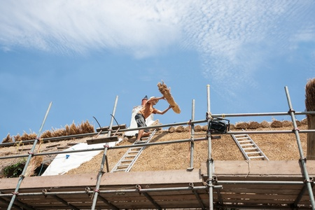 45 to 50 years old: Dunsford, England; July 23, 2013; roof thatchers replacing a traditional thatched roof a English rural town