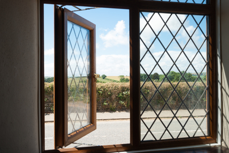 land locked: Country view through partly open Victorian style window