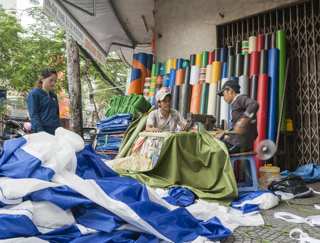 min: Ho Chi Min City, Vietnam - October 12, 2013  Vietnam, Saigon, Ho Chi Min City  workers sewing tarpaulins in their work place, a street corner pavement   A feature of Asian cities is the use of streets and pavements for shops, workshops and cafes