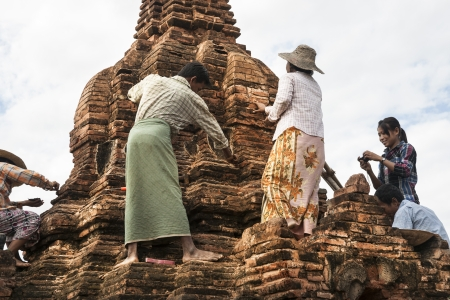 archaeologists: Bagan, Myanmar - October 29, 2013  Archaeologists investigate standing on the ancient brick structure  a small pagoda in Bagan Myanmar travel and people images