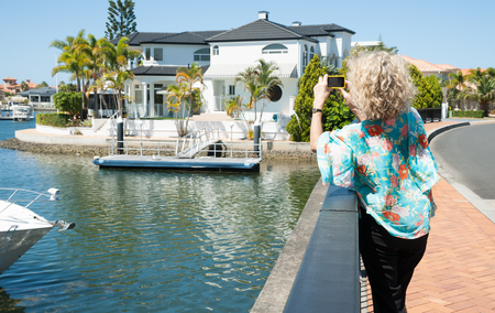 exclusive photo: Tourist takes a photo in exclusive suburb on mobile device  Stock Photo