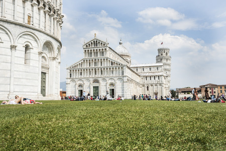 campo dei miracoli: Pisa, Italy. - April 23, 2011: Tourists looking at the Roman architectural structures of the Baptistry, the Duomo Pisa and the Leaning tower, some resting up on the lawn in front in the Piazza del Duomo, Pisa, Italy. Editorial