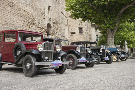 gordes: Gordes, France - May 1, 2011 - row of vintage cars parked along historic stone wall in Gordes, walled hillside village in France. Editorial