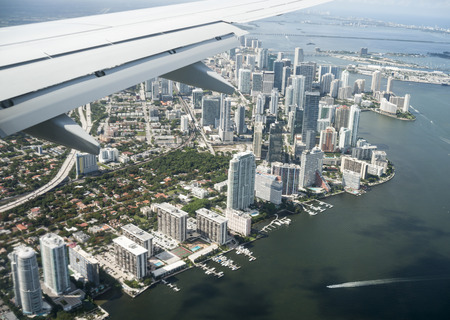 Arriving by air at Miami, the city skyline below, through plane window.
