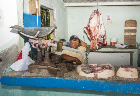TRINIDAD, CUBA - JULY 3, 2012; Butcher rests behind counter waiting for customer in village butchery  in Trinidad, Cuba.