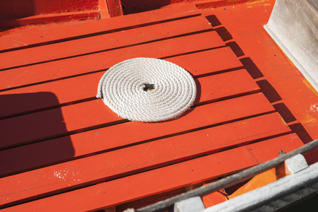 coiled rope: Coiled rope on boat floor.