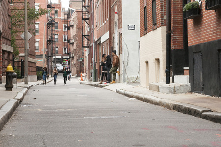 backstreet: BOSTON, USA - OCTOBER 14, 2014; youth stand aimlessly in backstreet smoking while another group walks up the street. Editorial