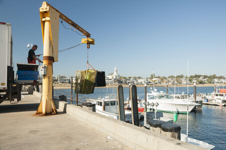 unloading: PROVINCETOWN, USA - OCTOBER 18, 2014; Unloading equipment from fishing boat on the wharf
