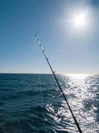 schittering: Zon flare en schittering over de zee en boven een hengel.