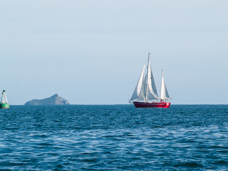ketch: Red ketch yacht heads for the Tauranga harbour, with Karewa Island behind.