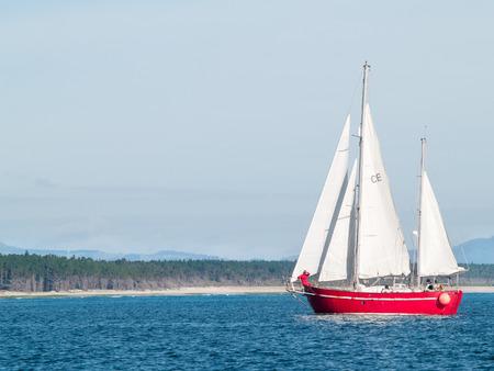 ketch: Red ketch yacht heads for the Tauranga harbour, with Matakana Island behind.