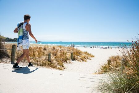male teenager: MOUNT MAUNGANUI, NEW ZEALAND-JANUARY 22 2015; youth walks to beach on hot summer day, carrying his towel  at Mount Maunganui Mount, New Zealand. the beaches are a key summer destinations. Editorial