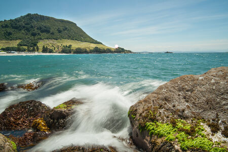 foreshore: Mount Maunganui, Water rushing through rocky foreshore on Moturiki Island with the Mount in background.