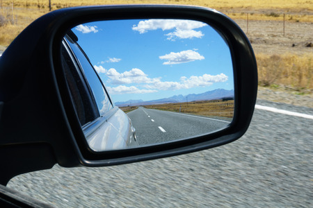 Long South Island road in rear vision mirror.