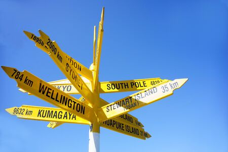 Signpost pointing cities and places around the world at the southern point of New zealand, Stirling Point , Bluff. Stock Photo