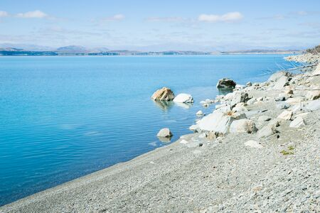 stoney: Lake Pukaki turquoise water and stoney beach. Snow feed lake in Canterbury, South Island NZ. Stock Photo