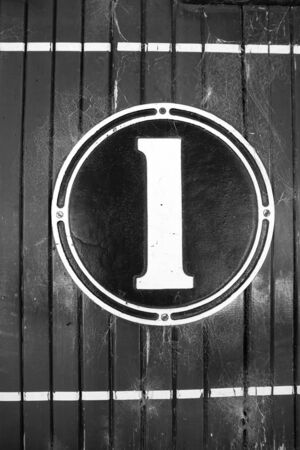 panelled: Numeral one, old fashioned sign, on circular cast metal and painted, mounted on wooden panelled wall in black and white retro style image. Stock Photo
