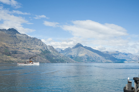 shores: Queenstown on shores of Lake Wakatipu with old steamer dwarfed in the lake by surrounding Remarkables mountain range of the Southern Alps.