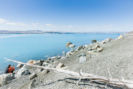mackenzie: Canterbury, New Zealand; February 15, 2015; Lake Pukaki, Canterbury, South Island New Zealand. The turquoise water, blue sky and grey stony foreshore with a tourist sitting amongst rocks taking photograph. Editorial